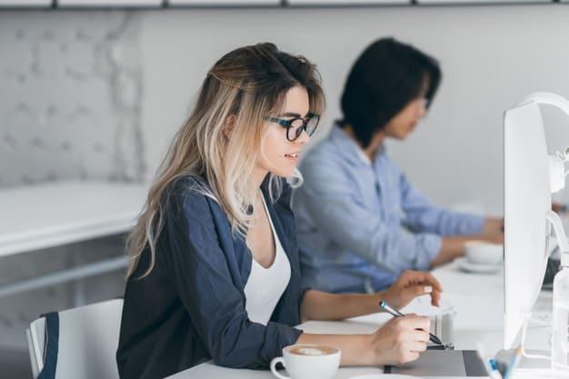 Expectativas da reforma tributária. Mulher trabalhando em frente ao computador enquanto segura uma caneta.